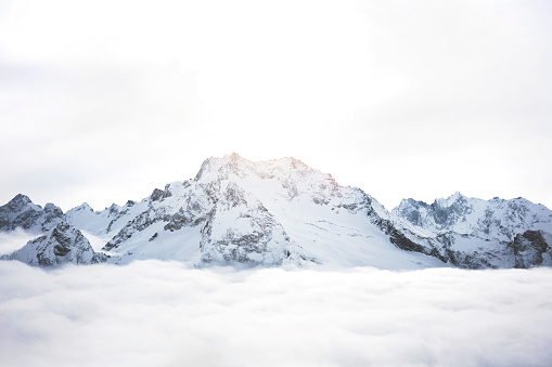 Snowy mountains above the clouds. Great winter massif of rocks 902643670
