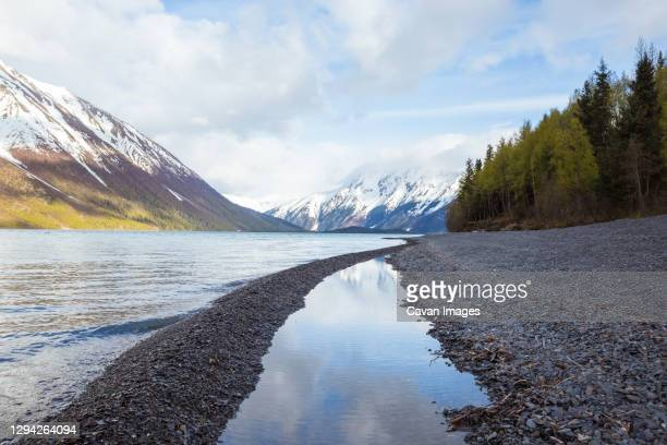 snowy mountains in clouds, viewed from shore of kenai lake, alaska - kenai mountains stock pictures, royalty-free photos & images