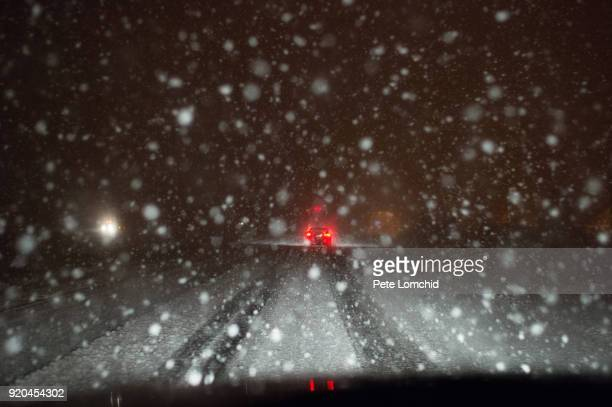 snowy road at night - winter weather stock photos and pictures