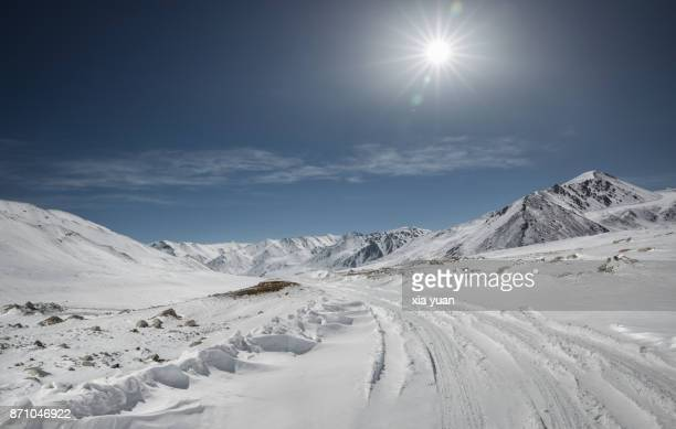 snowy road in mountains against sunlight - terreno extremo - fotografias e filmes do acervo