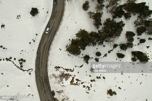 Snowy road in the Andorra Pyrenees mountains from above with car.