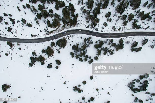 Snowy road in the Andorra Pyrenees mountains from above with cars.