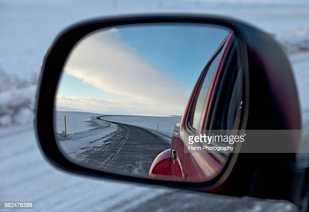 snowy road reflecting in the wing mirror of a 4x4 pick up truck