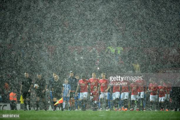 TOPSHOT A snowy start to the English FA Cup quarterfinal football match between Manchester United and Brighton and Hove Albion at Old Trafford in...