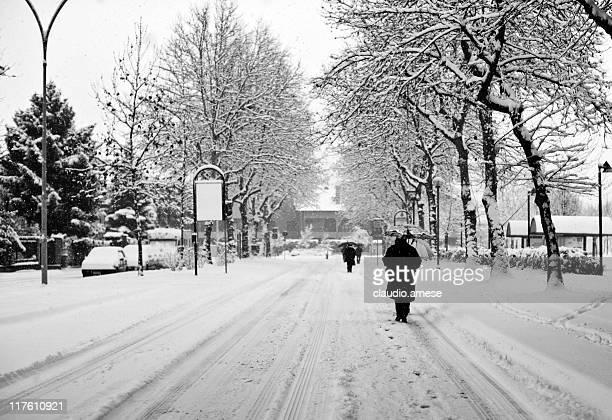 Strada innevata con le persone a piedi. Bianco e nero