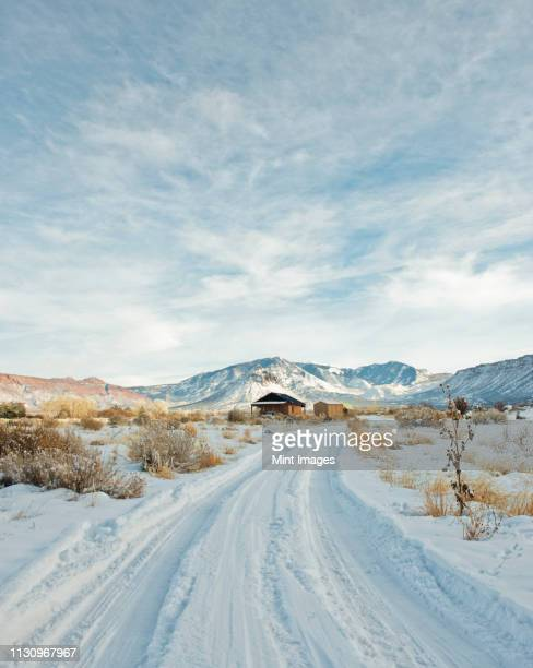 snowy trail leading to a remote house - utah stock pictures, royalty-free photos & images