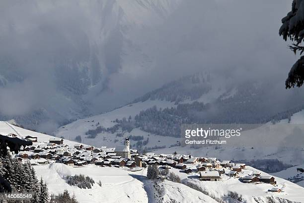 Snowy village with mountain range and valley in the background