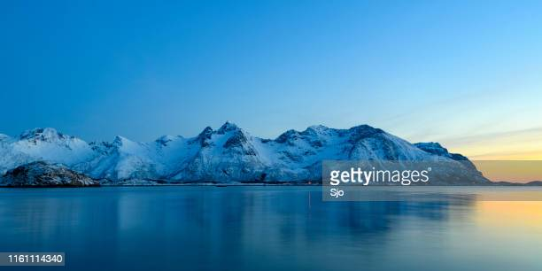 snowy winter landscape sunset over a fjord in the lofoten in norway - northern norway stock pictures, royalty-free photos & images