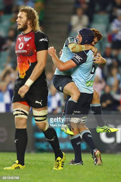 Snyman of the Bulls looks dejected as Andrew Kellaway and Dean Mumm of the Waratahs celebrate a try by Mumm during the round 12 Super Rugby match...