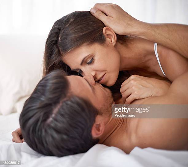 so close i can feel her heart beat! - man and woman cuddling in bed stock photos and pictures