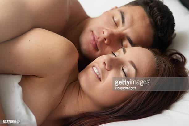 so close she can feel his heart beat - romantic young couple sleeping in bed stock photos and pictures