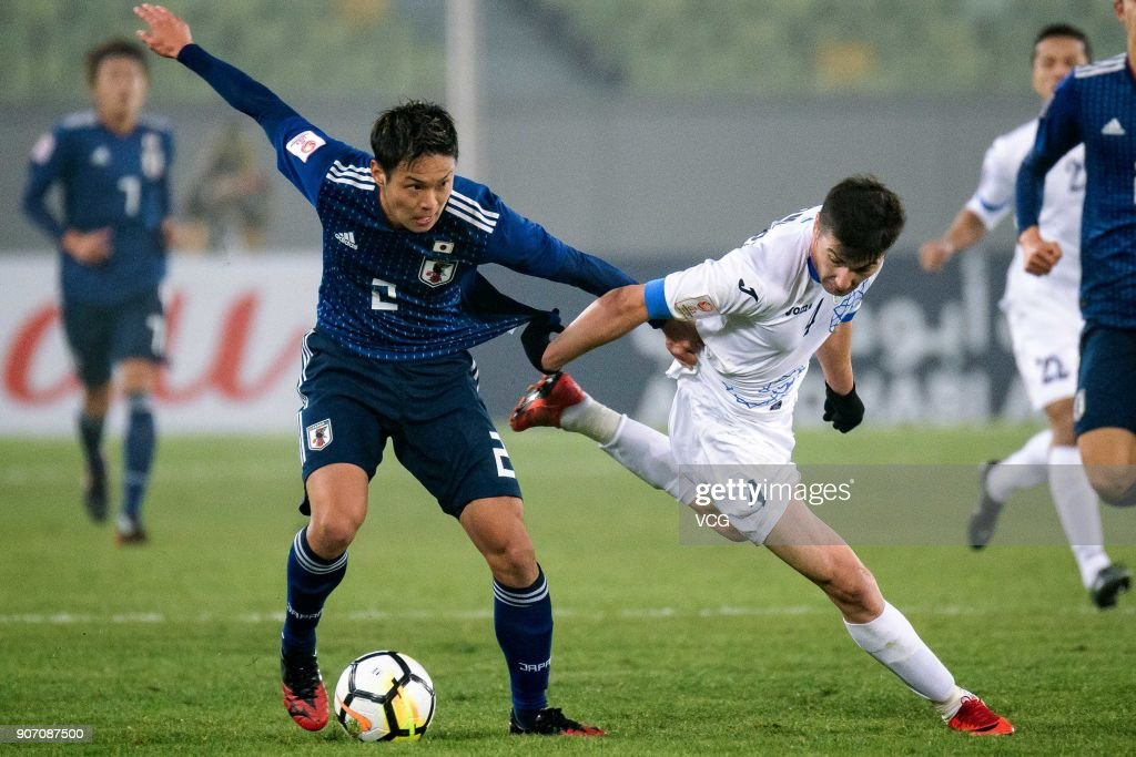 So Fujitani #2 of Japan and Akramjon Komilov #4 of Uzbekistan compete for the ball during the AFC U-23 Championship quarter-final match between Japan and Uzbekistan at Jiangyin Stadium on January 19, 2018 in Jiangyin, Jiangsu Province of China.