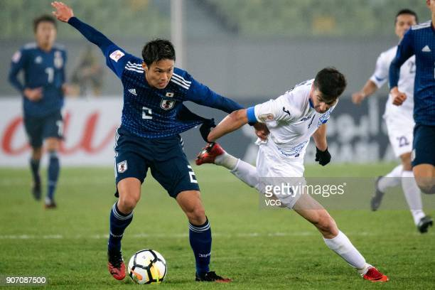 So Fujitani of Japan and Akramjon Komilov of Uzbekistan compete for the ball during the AFC U23 Championship quarterfinal match between Japan and...