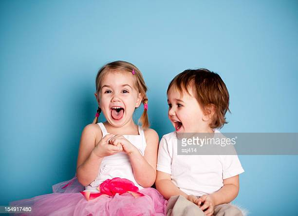 so funny! girl and boy laughing hysterically - zus stockfoto's en -beelden