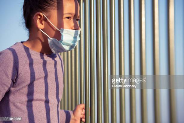so interestingly, what's going outside during the coronavirus pandemic? a kid in face mask looking away through the fence bars. - child behind bars stock pictures, royalty-free photos & images