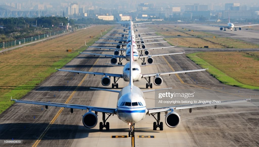 so many airplanes are in line on the runway waiting for take off : Stock Photo