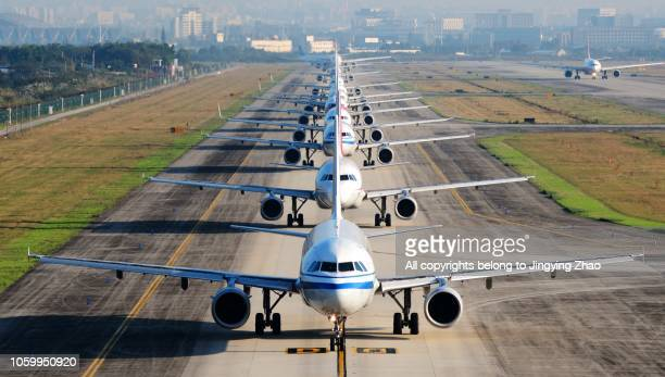 so many airplanes are in line on the runway waiting for take off - flugzeug stock-fotos und bilder
