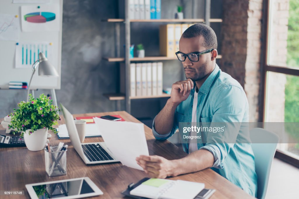 So nerd and focused. Young handsome afro student is concentrated on studying. He is in a casual outfit with project at his work station : Stock Photo