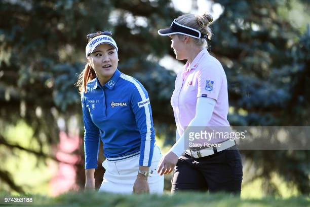 So Yeon Ryu of South Korea and Brooke Henderson of Canada walk to the third tee during the first round of the Meijer LPGA Classic for Simply Give at...