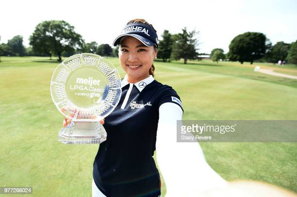 So Yeon Ryu of South Korea imitates a selfie as she poses with the championship trophy during the final round of the Meijer LPGA Classic for Simply...