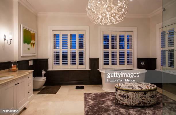 Soaking tub and modern chandelier in luxury bathroom at night