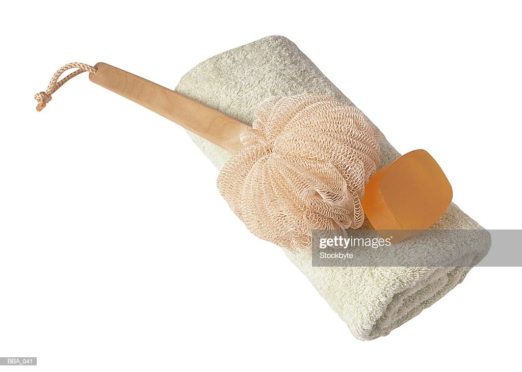 Soap bar and back scrubber on towel : Foto de stock