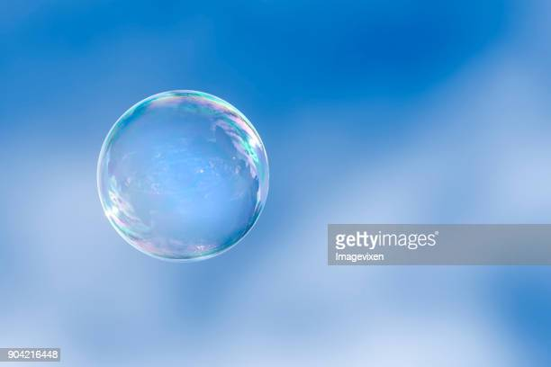 Soap bubble floating in a blue sky