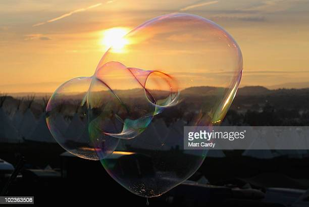 A soap bubble floats against the backdropThe first of the 140000 music fans due at this year's Glastonbury Festival enjoy the sunset at Worthy Farm...