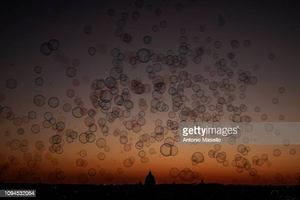 Soap bubbles are seen in front of St Peter's Basilica at sunset on February 6 2019 in Rome Italy