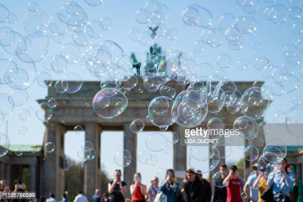 Soap bubbles hover through the air in front of Berlin's landmark the Brandenburg Gate on April 8 2019 / Germany OUT