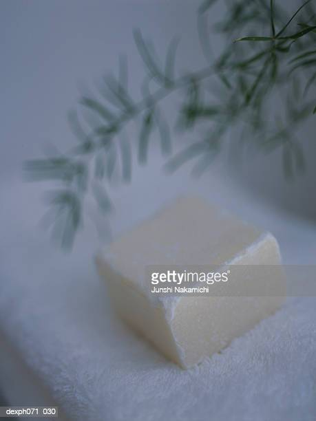 Soap lying on folded white towels, close up