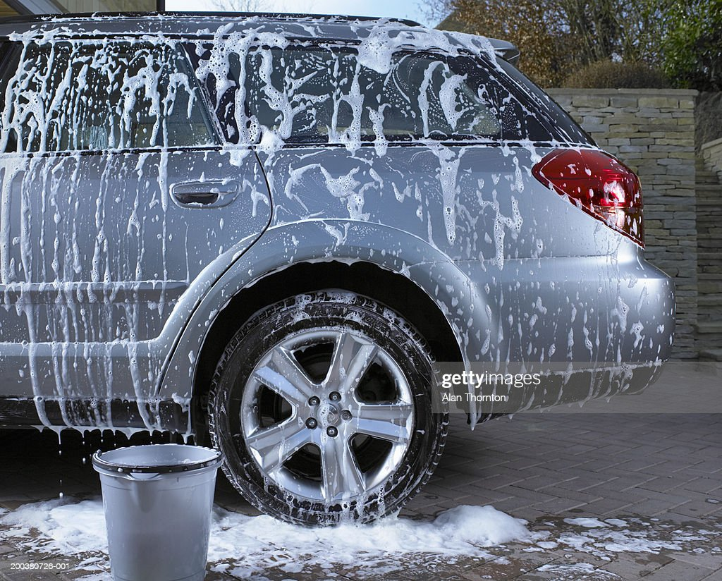 Soap suds and water on car : Stock Photo