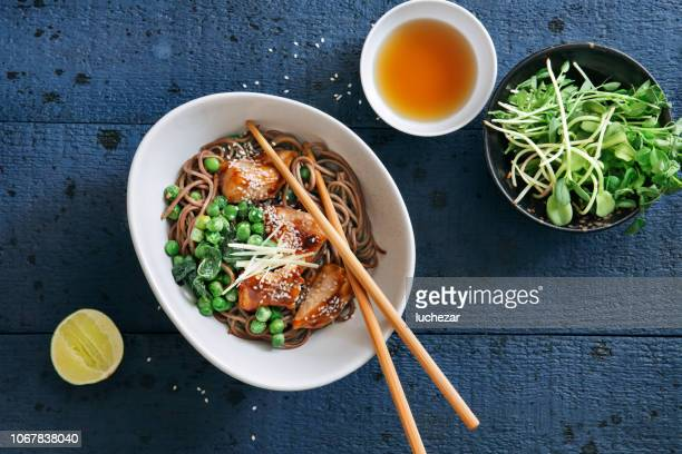soba with glazed chicken, sesame, green pea and sprouts - miso sauce stock pictures, royalty-free photos & images