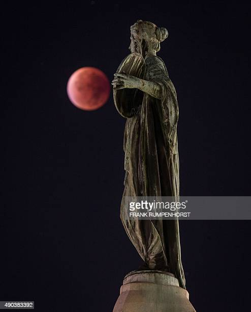 A socalled 'blood moon' can be seen behind a statue during a total lunar eclipse in Frankfurt am Main western Germany on September 28 2015 Skygazers...