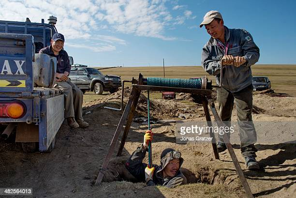 """So-called """"ninja"""" in the Sharyngol district of Mongolia, is lowered into a small hole about 10 feet deep where he will crawl around the underground..."""
