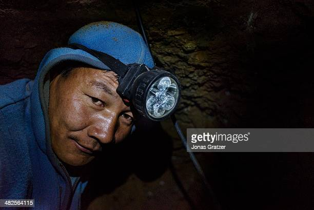 """So-called """"ninja"""" in the Sharyngol district of Mongolia uses power tools to dig further into an underground tunnel in hope to find a few grams of..."""