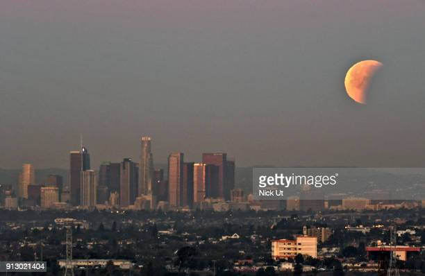 A socalled 'super blue blood moon' descends over downtown Los Angeles skyline January 31 2018 seen from Whittier California The Super Blue Blood Moon...