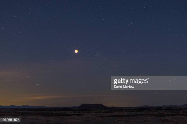 A socalled 'super blue blood moon' is seen during total eclipse above Amboy Crater a cinder cone volcano in the Mojave Desert on January 31 2018 near...