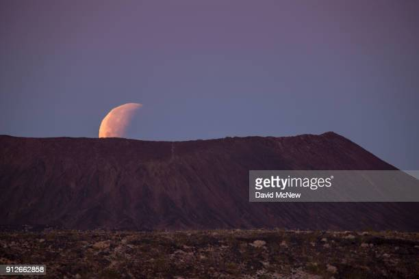 A socalled 'super blue blood moon' sets behind Amboy Crater a cinder cone volcano in the Mojave Desert at the end of its total eclipse on January 31...