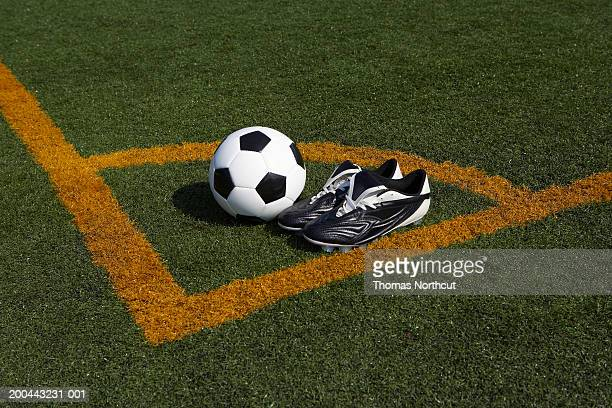 Soccer ball and cleats in corner of soccer pitch, elevated view