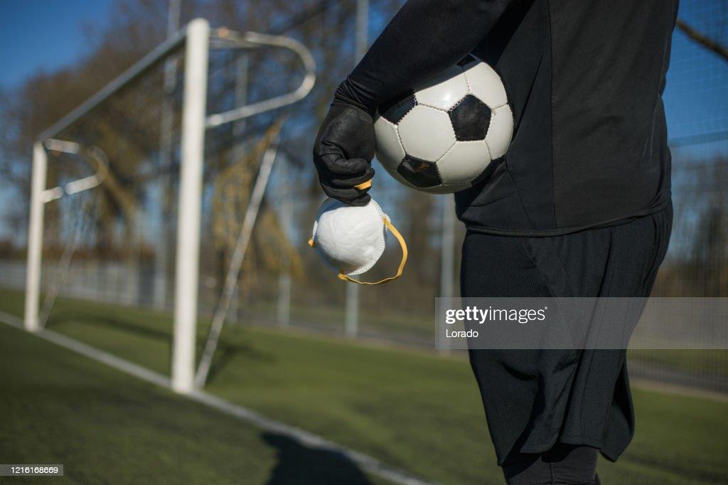 Soccer ball and virus mask : Stock Photo