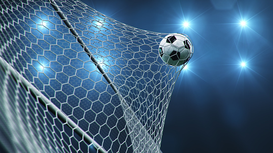 Soccer ball flew into the goal. Soccer ball bends the net, against the background of flashes of light. Soccer ball in goal net on blue background. A moment of delight. 3D illustration 1197582798