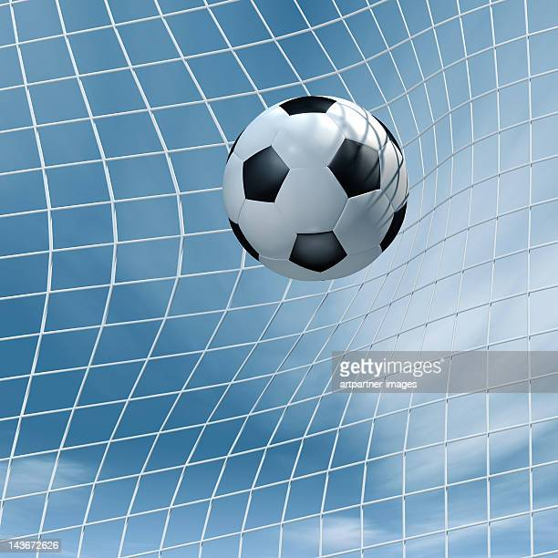 Soccer ball flying into a goal