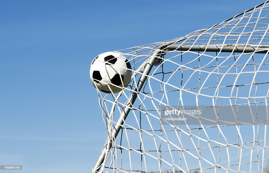 Soccer ball hits the net and makes a goal : Stock Photo