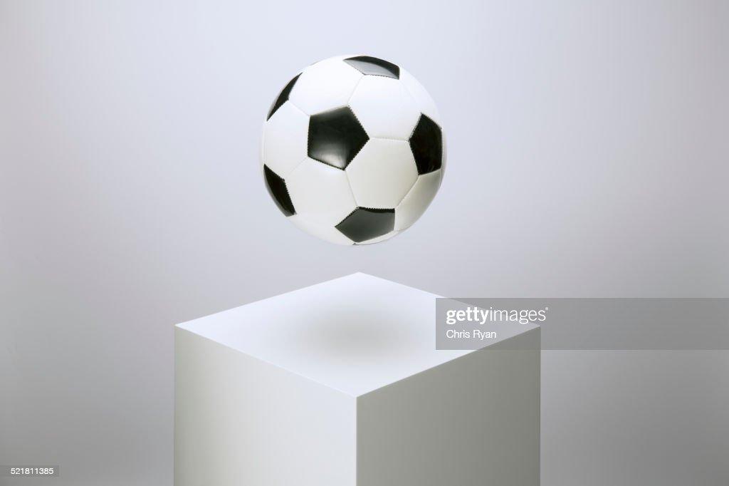 Soccer ball hovering over pedestal : Stock Photo