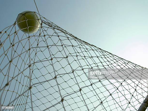 a soccer ball in a goal - soccer goal stock pictures, royalty-free photos & images