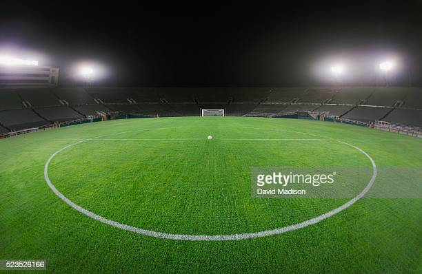 soccer ball in empty stadium - football pitch stock pictures, royalty-free photos & images