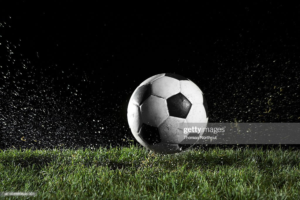 Soccer ball in motion over grass : Stock Photo