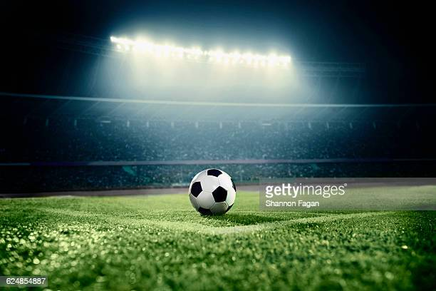 soccer ball in sports field in stadium at night - bal stockfoto's en -beelden