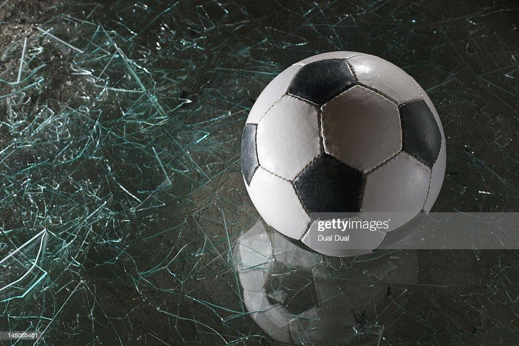 A soccer ball on broken glass : Foto de stock
